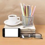 Schreibtisch: Kaffee und Telefon mit Schlüssel, Brillen, Stapel des Buches Stockbild