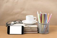 Schreibtisch: Kaffee und Telefon mit Schlüssel, Brillen, Stapel des Buches Stockbilder
