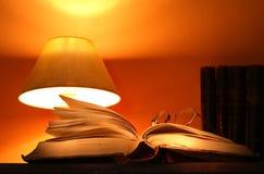 Schreibtisch-Lampe und alte Bücher Stockbilder