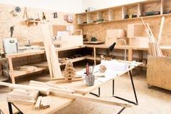 Schreibtisch mit Berufsinstrumenten sind in der Schreinerei Stockbild