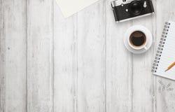 Schreibtisch mit freiem Raum für Text Kamera, Tasse Kaffee, Papier, Notizblock, Bleistift auf weißem Holztisch Lizenzfreies Stockfoto