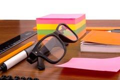 Schreibtisch mit Gläsern sperren Bleistiftmachthaber und andere Büroeinzelteile ein Stockfotos