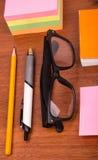 Schreibtisch mit Gläsern sperren Bleistiftmachthaber und andere Büroeinzelteile ein Lizenzfreie Stockfotos