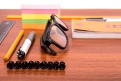 Schreibtisch mit Gläsern sperren Bleistiftmachthaber und andere Büroeinzelteile ein Stockfoto