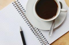 Schreibtisch mit Kaffee und Notizbuch Lizenzfreie Stockbilder