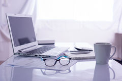 Schreibtisch mit Laptop-Computer auf weißem Schreibtisch Lizenzfreie Stockfotografie