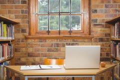 Schreibtisch mit Laptop, Gläsern und Hauptbuch auf ihm Stockfotografie