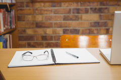 Schreibtisch mit Laptop, Gläsern und Hauptbuch auf ihm Stockfoto