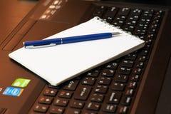Schreibtisch mit Laptop, intelligentem Telefon, Notizbüchern, Stiften, Brillen und einer Tasse Tee Seitenwinkelsicht stockfotografie
