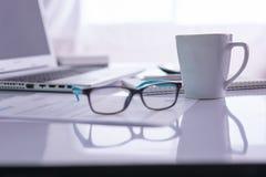 Schreibtisch mit Laptop, Stifte, Gläser Stockfotografie
