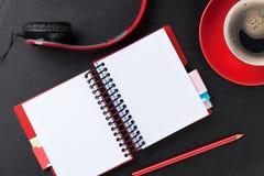 Schreibtisch mit Notizblock, Kaffee und Kopfhörern Stockfotografie
