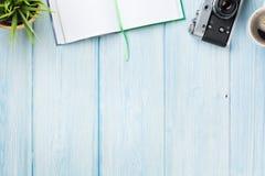 Schreibtisch mit Notizblock, Kamera, Kaffee und Blume Stockfotos
