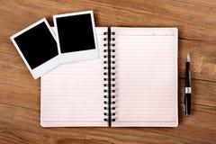 Schreibtisch mit offenem Notizbuch und leeren Fotos Stockbilder