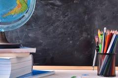 Schreibtisch mit Schulwerkzeugen und -tafel Lizenzfreie Stockbilder