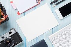 Schreibtisch mit Versorgungen, Kamera und leerer Karte Stockfotografie