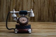 Schreibtisch-Uhr mit Antic Telefon-Form auf Brown-Hintergrund Lizenzfreie Stockfotografie