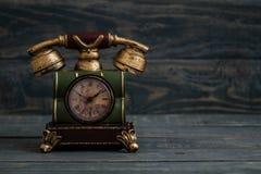 Schreibtisch-Uhr mit antikem Telefon-Design auf blauem Hintergrund Lizenzfreie Stockfotos