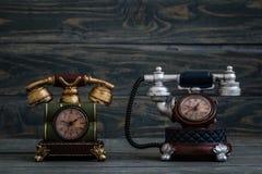Schreibtisch-Uhren mit antikem Telefon-Design auf blauem Hintergrund Lizenzfreie Stockfotografie