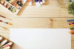 Schreibtisch von Künstlerfarbbleistiften und -papier auf hölzerner Tabelle stockfotografie