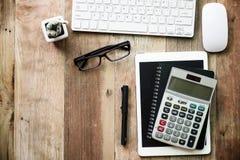 Schreibtischarbeit mit Computertastatur, Gläsern, Tabletten-PC und smartph Lizenzfreie Stockfotografie