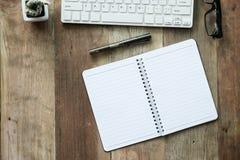 Schreibtischarbeit mit Computertastatur, -gläsern und -notizbuch Stockbilder