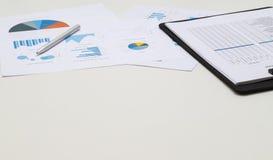 Schreibtischarbeitsplatz mit Check-Listen-Diagramm und Geschäftsdiagrammen Stockbild