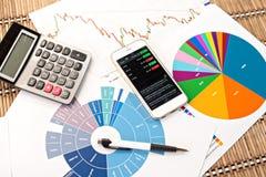 Schreibtischarbeitsplatz mit PC, Taschenrechner und Telefon auf Diagrammen Stockfotografie