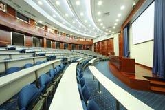 Schreibtische, blaue Sitze, hölzernes Podium Stockfotografie