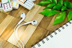 Schreibtische mit Kopfhörer und Notizbuch und Domino auf Tabelle Stockfotografie