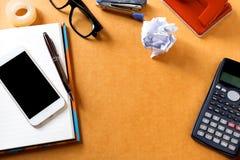 Schreibtischhintergrund mit Taschenrechner, Augengläser auf Notizblock a Stockbild