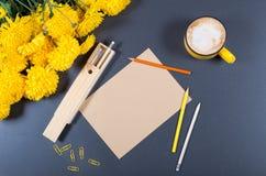 Schreibtischoberfläche mit Blatt Papier Kraftpapier, Farbbleistifte, hölzernen Bleistiftkasten, große Schale Cappuccino und Bünde Lizenzfreie Stockfotografie