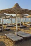 Schreibtischstühle und -regenschirm auf einem Strand Stockfotos
