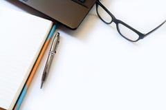 Schreibtischtabelle mit Computer, Laptop, Gläser, Versorgungen, Anmerkung Stockfoto