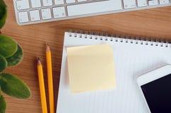 Schreibtischtabelle mit Computer, Smartphone, Versorgungen, Blume und leerem Notizaufkleber, Draufsicht lizenzfreie stockbilder