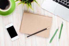 Schreibtischtabelle mit Computer, Versorgungen, Kaffeetasse und Blume