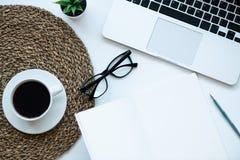Schreibtischtabelle mit dem Laptop, Gläsern, Tasse Kaffee und Versorgungen, lokalisiert auf weißem Hintergrund Draufsicht mit Kop stockfotografie