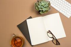 Schreibtischtabelle mit der Notizbuchtastaturnotizbuchteeschale und -gläsern Schein herauf Schablone Beschneidungspfad eingeschlo lizenzfreie stockfotos