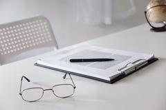 Schreibtischtabelle mit Glasstiftbleistift und -Weltkarte lizenzfreie stockfotografie