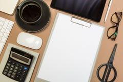 Schreibtischtabelle mit Klemmbretttastaturnotizbuch-Kaffeetassetaschenrechnergläsern und -scheren Spott herauf Schablone Beschnei lizenzfreies stockfoto
