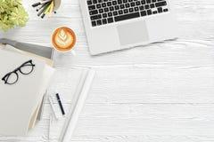 Schreibtischtabelle mit labtop Computer, intelligentem Telefon der leeren Zeitschrift, Brillen und Kaffeetasse Draufsicht mit Kop Stockfotografie