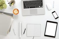 Schreibtischtabelle mit labtop Computer, intelligentem Telefon der leeren Zeitschrift und Kaffeetasse Weiße Tabelle der Draufsich Lizenzfreie Stockfotografie