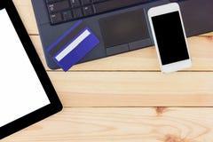 Schreibtischtabelle mit Laptop-Computer, Smartphone des leeren Bildschirms, Tablette des leeren Bildschirms und Kreditkarte Drauf lizenzfreies stockfoto