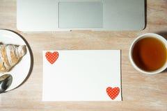 Schreibtischtabelle mit Laptop-Computer, Tee und Hörnchen Beschneidungspfad eingeschlossen Lizenzfreie Stockfotografie