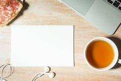 Schreibtischtabelle mit Laptop-Computer, Tee und Sandwich mit Wurst Beschneidungspfad eingeschlossen Stockfotos