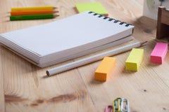 Schreibtischtabelle mit Notizbuch und Versorgungen Lizenzfreie Stockfotos