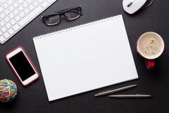 Schreibtischtabelle mit PC, Notizblock, Gläsern, Kaffee und Telefon Stockfotos