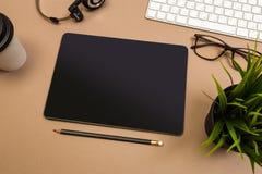 Schreibtischtabelle mit Tablettentastaturkopfhörern Kaffee und Gläser Schein herauf Schablone Beschneidungspfad eingeschlossen stockfotografie