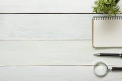 Schreibtischtabelle mit Versorgungen Beschneidungspfad eingeschlossen Kopieren Sie Raum für Text Notizblock, Stift, Lupe, Blume Lizenzfreie Stockfotos