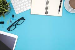 Schreibtischtabelle mit Versorgungen und Computer auf blauem Hintergrund Stockfotografie