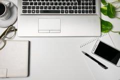 Schreibtischtischplatteansicht und Versorgungen, Laptop, Schale schwarzer Kaffee, Gläser, Anlage, Mobiltelefon auf weißem Hinterg stockfotos